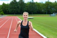 Υγιής κατάλληλη νέα γυναίκα που τρέχει σε μια διαδρομή Στοκ εικόνες με δικαίωμα ελεύθερης χρήσης