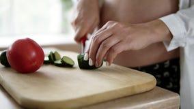 Υγιής κατανάλωση, εγκυμοσύνη, τρόφιμα και έννοια ανθρώπων - όμορφη κουζίνα αγγουριών εγκύων γυναικών τέμνουσα στο σπίτι στο στηθό φιλμ μικρού μήκους