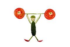 Υγιής κατανάλωση. Αστείο λίγο άτομο των φετών αγγουριών αυξάνει το τ Στοκ εικόνες με δικαίωμα ελεύθερης χρήσης