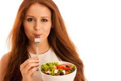 Υγιής κατανάλωση - η γυναίκα τρώει ένα κύπελλο της ελληνικής σαλάτας που απομονώνεται Στοκ Εικόνες