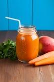 Υγιής καταφερτζής μήλων καρότων σε ένα βάζο στο μπλε ξύλινο υπόβαθρο Στοκ εικόνα με δικαίωμα ελεύθερης χρήσης