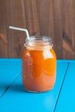 Υγιής καταφερτζής μήλων καρότων σε ένα βάζο στο μπλε ξύλινο υπόβαθρο Στοκ φωτογραφία με δικαίωμα ελεύθερης χρήσης