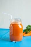 Υγιής καταφερτζής μήλων καρότων σε ένα βάζο στο μπλε ξύλινο υπόβαθρο Στοκ Φωτογραφία