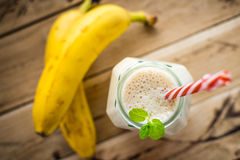 Υγιής καταφερτζής μπανανών στο άσπρο ξύλινο υπόβαθρο στοκ εικόνα
