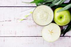 Υγιής καταφερτζής της Apple με την πρασινάδα στο άσπρο ξύλο Στοκ Φωτογραφίες