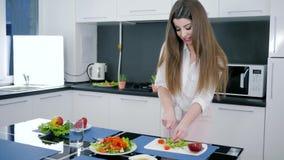 Υγιής νέα γυναίκα με το μαχαίρι που τεμαχίζει το πράσινο μπρόκολο για τη φρέσκια σαλάτα στον πίνακα κουζινών φιλμ μικρού μήκους