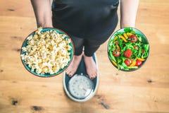 Υγιής νέα γυναίκα που εξετάζει τα υγιή και ανθυγειινά τρόφιμα, που προσπαθούν να κάνει τη σωστή επιλογή στοκ εικόνες