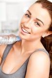 Υγιής νέα γυναίκα που κρατά ένα μπουκάλι νερό Στοκ φωτογραφία με δικαίωμα ελεύθερης χρήσης