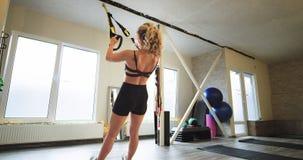 Υγιής νέα κυρία τρόπου ζωής που ασκεί μια άσκηση TRX για το τέντωμα του σώματος σε ένα σύγχρονο φωτεινό αεροβικό εξοπλισμένο στού φιλμ μικρού μήκους