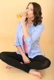 Υγιής νέα συνεδρίαση γυναικών στο πάτωμα που πίνει το φρέσκο χυμό από πορτοκάλι Στοκ Εικόνα