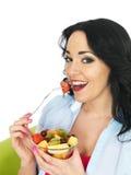 Υγιής νέα φρέσκια αντιμέτωπη γυναίκα που τρώει μια ζωηρόχρωμη εξωτική σαλάτα νωπών καρπών Στοκ Εικόνες