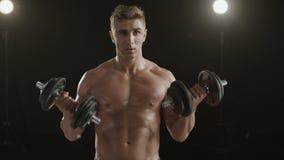 Υγιής νεαρός άνδρας που εκπαιδεύει τους και τους δύο δικέφαλους μυς του απόθεμα βίντεο