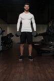 Υγιής νεαρός άνδρας που κάνει την άσκηση για τους δικέφαλους μυς Στοκ εικόνες με δικαίωμα ελεύθερης χρήσης