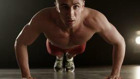 Υγιής νεαρός άνδρας που κάνει το ώθηση-UPS φιλμ μικρού μήκους