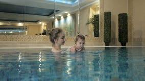 Υγιής οικογένεια Κοριτσάκι διδασκαλίας μητέρων που κολυμπά στη λίμνη απόθεμα βίντεο