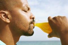 υγιής οργανικός τροφίμων Πορτρέτο του σκοτεινού ξεφλουδισμένου τύπου που πίνει το νόστιμο φρέσκο χυμό από πορτοκάλι Αφρικανική συ στοκ εικόνα με δικαίωμα ελεύθερης χρήσης