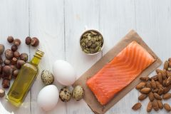 υγιής οργανικός τροφίμων Προϊόντα με τα υγιή λίπη Omega 3 Omega 6 Συστατικά και προϊόντα: καρύδια αβοκάντο ελαιολάδου σολομών πεσ στοκ φωτογραφίες