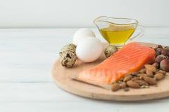 υγιής οργανικός τροφίμων Προϊόντα με τα υγιή λίπη Omega 3 Omega 6 Συστατικά και προϊόντα: καρύδια αβοκάντο ελαιολάδου σολομών πεσ στοκ φωτογραφία