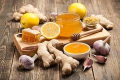 Υγιής πίνακας τροφίμων με το μέλι, την πιπερόριζα, το σκόρδο και το λεμόνι Στοκ Εικόνα