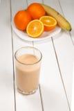 Υγιής πιείτε τους καταφερτζήδες πορτοκαλιών και μπανανών στον ξύλινο πίνακα Στοκ Εικόνα