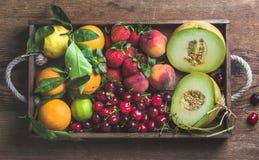 Υγιής ποικιλία θερινών φρούτων Πεπόνι, γλυκά κεράσια, ροδάκινο, φράουλα, πορτοκάλι και λεμόνι στον ξύλινο δίσκο πέρα από αγροτικό Στοκ Φωτογραφίες