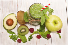Υγιής πράσινος καταφερτζής με την μπανάνα, το σπανάκι, το αβοκάντο και το ακτινίδιο στα μπουκάλια ενός γυαλιού σε έναν αγροτικό Στοκ εικόνες με δικαίωμα ελεύθερης χρήσης