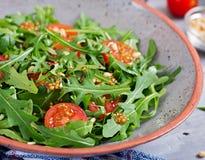 Υγιής σαλάτα με το arugula, τις ντομάτες και τα καρύδια πεύκων Στοκ εικόνες με δικαίωμα ελεύθερης χρήσης