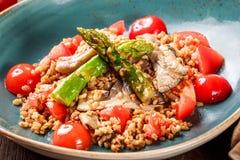 Υγιής σαλάτα του κουάκερ κριθαριού με το σπαράγγι, τις ντομάτες και τα μανιτάρια στο πιάτο Τρόφιμα Vegan Στοκ εικόνα με δικαίωμα ελεύθερης χρήσης
