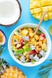 Υγιής σαλάτα φρούτων με το μάγκο, τον ανανά, το ροδάκινο και το pitaya στο φωτεινό μπλε υπόβαθρο Στοκ Εικόνες