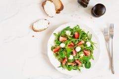 Υγιής σαλάτα με το σπανάκι, το arugula και τις φράουλες στο πιάτο Στοκ Φωτογραφίες