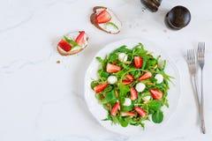 Υγιής σαλάτα με το σπανάκι, το arugula και τις φράουλες στο πιάτο Στοκ Φωτογραφία