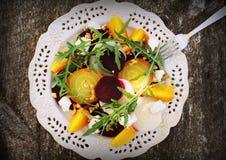 Υγιής σαλάτα τεύτλων με τα κόκκινα, άσπρα, χρυσά τεύτλα, arugula, καρύδια, τυρί φέτας στο ξύλινο υπόβαθρο Στοκ Φωτογραφία