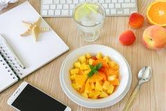 Υγιής σαλάτα φρούτων πρόχειρων φαγητών του ροδάκινου, βερίκοκο, πορτοκάλι στον εργασιακό χώρο Στοκ Εικόνα