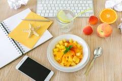 Υγιής σαλάτα φρούτων πρόχειρων φαγητών του ροδάκινου, βερίκοκο, πορτοκάλι στον εργασιακό χώρο Στοκ Φωτογραφίες