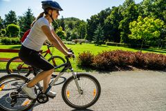 Υγιής τρόπος ζωής - άνθρωποι που οδηγούν τα ποδήλατα στο πάρκο πόλεων Στοκ εικόνα με δικαίωμα ελεύθερης χρήσης