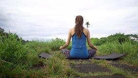 υγιής τρόπος ζωής έννοιας Η γυναίκα meditates στη γιόγκα θέτει υποστηρίξτε την όψη απόθεμα βίντεο