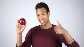 Υγιής τρόπος ζωής, αφροαμερικανός άτομο που παρουσιάζει την κόκκινους Apple και αντίχειρες επάνω στη χειρονομία Στοκ Εικόνες