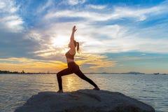 Υγιής τρόπος ζωής γυναικών γιόγκας που ασκεί τη ζωτικής σημασίας γιόγκα meditate και ενέργειας στο βράχο κοντά στην ακτή, Στοκ Εικόνα