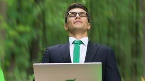 Υγιής υπάλληλος που παίρνει τη βαθιά εισπνοή εργαζόμενος στο lap-top στο πάρκο, καθαρός αέρας απόθεμα βίντεο
