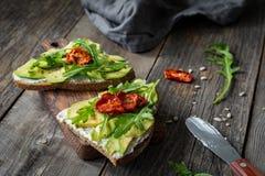 Υγιής φρυγανιά με το αβοκάντο, το τυρί αιγών και το arugula Στοκ Φωτογραφίες