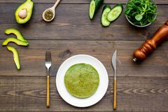 Υγιής φυτική τηγανίτα Οι τηγανίτες σπανακιού εξυπηρέτησαν με το αγγούρι, το αβοκάντο και την πρασινάδα στη σκοτεινή ξύλινη κορυφή στοκ εικόνες με δικαίωμα ελεύθερης χρήσης