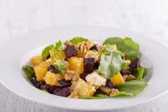 Υγιής χορτοφάγος σαλάτα με τα παντζάρια, το πράσινο arugula, το πορτοκάλι, το τυρί φέτας και τα ξύλα καρυδιάς στο άσπρο πιάτο Στοκ φωτογραφία με δικαίωμα ελεύθερης χρήσης