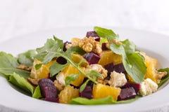 Υγιής χορτοφάγος σαλάτα με τα παντζάρια, το πράσινο arugula, το πορτοκάλι, το τυρί φέτας και τα ξύλα καρυδιάς στο άσπρο πιάτο Στοκ Εικόνα