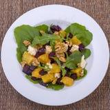 Υγιής χορτοφάγος σαλάτα με τα παντζάρια, το πράσινο arugula, το πορτοκάλι, το τυρί φέτας και τα ξύλα καρυδιάς στο άσπρο πιάτο, το Στοκ Φωτογραφία