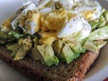 υγιής χορτοφάγος τροφίμων Αβοκάντο με τα ελεύθερα αυγά σειράς στο καφετί ψωμί Στοκ Φωτογραφία