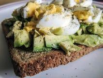 υγιής χορτοφάγος τροφίμων Αβοκάντο με τα ελεύθερα αυγά σειράς στο καφετί ψωμί Στοκ Φωτογραφίες
