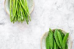 υγιής χορτοφάγος τροφίμων Σπαράγγι και μπιζέλι στην γκρίζα τοπ άποψη υποβάθρου πετρών copyspace Στοκ Φωτογραφία