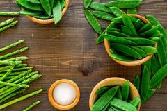 υγιής χορτοφάγος τροφίμων Σπαράγγι και μπιζέλι στη σκοτεινή ξύλινη τοπ άποψη υποβάθρου copyspace Στοκ εικόνα με δικαίωμα ελεύθερης χρήσης