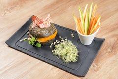 _υγιής burger με hamon, ντομάτα, μικροϋπολογιστής πρασινίζω και μαύρος wholegrain κουλούρι, λαχανικό ραβδί μαύρος πλάκα πίνακας  στοκ εικόνα