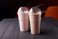 Υγιή και νόστιμα κοκτέιλ φρούτων όπως το κούνημα καταφερτζήδων ή γάλακτος στα πλαστικά φλυτζάνια στοκ φωτογραφία με δικαίωμα ελεύθερης χρήσης
